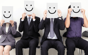People in business attire sitting in chairs against a white wall holding cardboard smiling faces in front of their head
