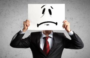 Businessman in suit holding cardboard sad face in front of head